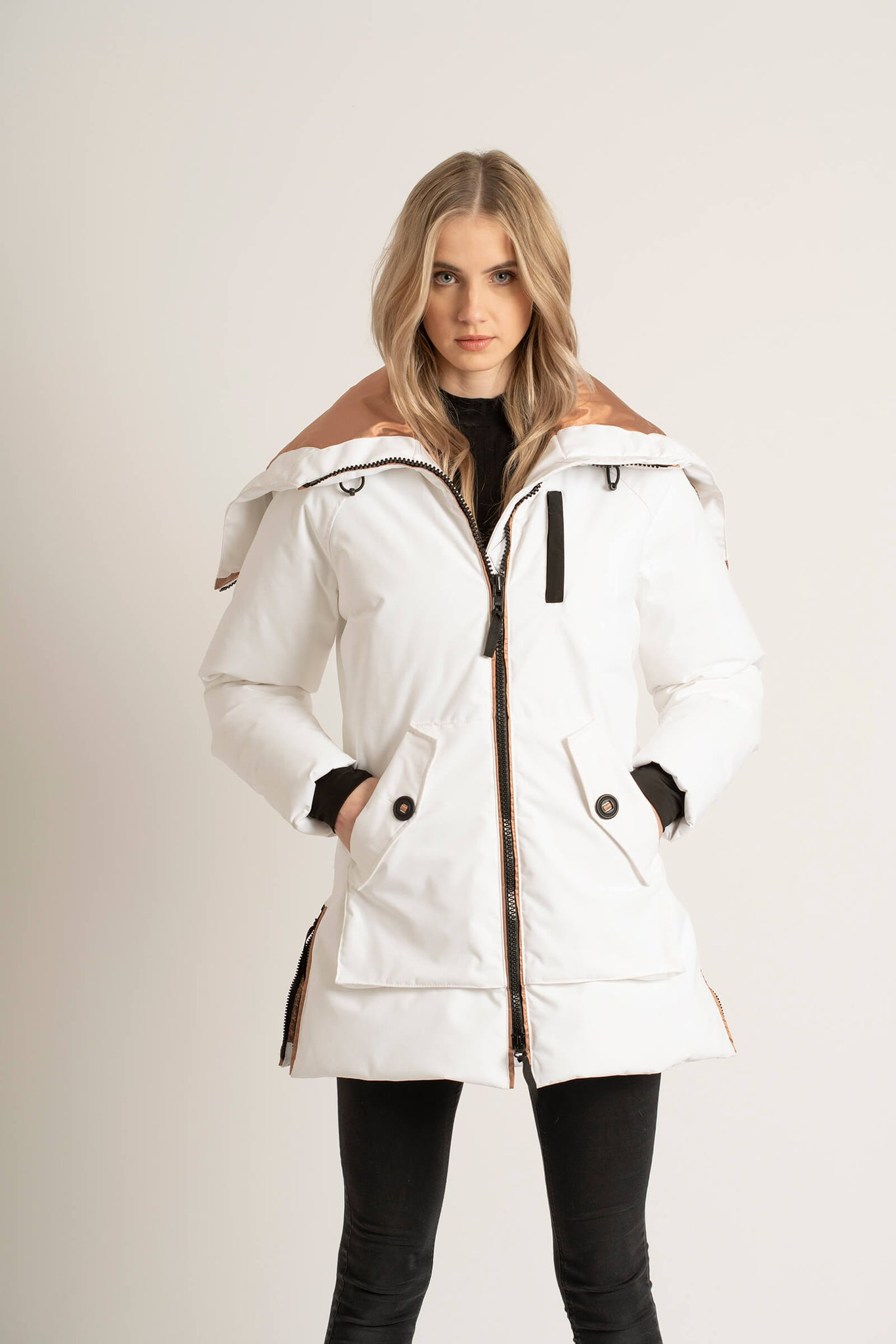 Women wearing a Tough Duck Black Widgeon Mid-Length Parka in white with her hands in her pocket.