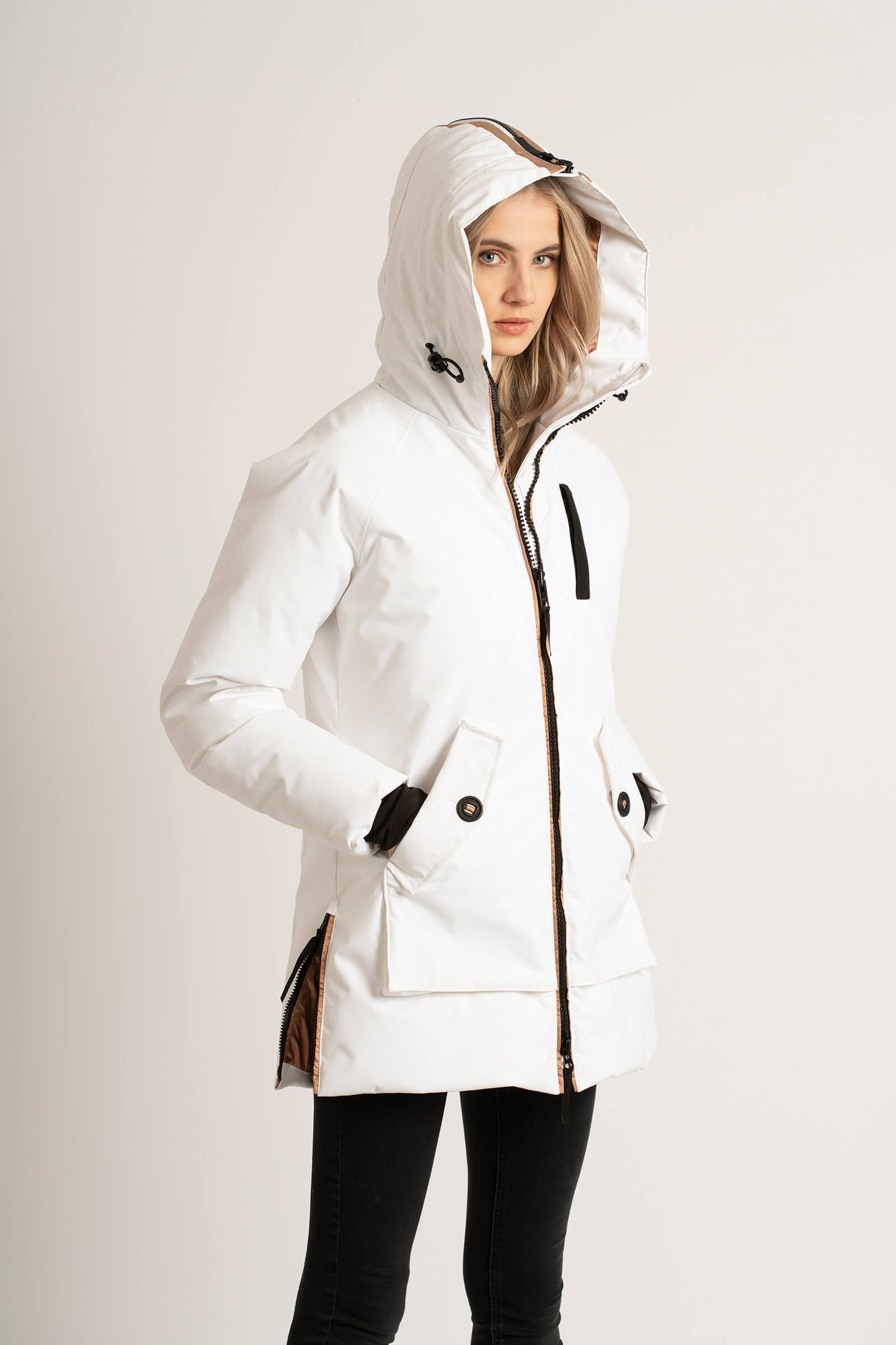 Women wearing a Tough Duck Black Widgeon Mid-Length Parka in white with her hands in her pocket and hood up.