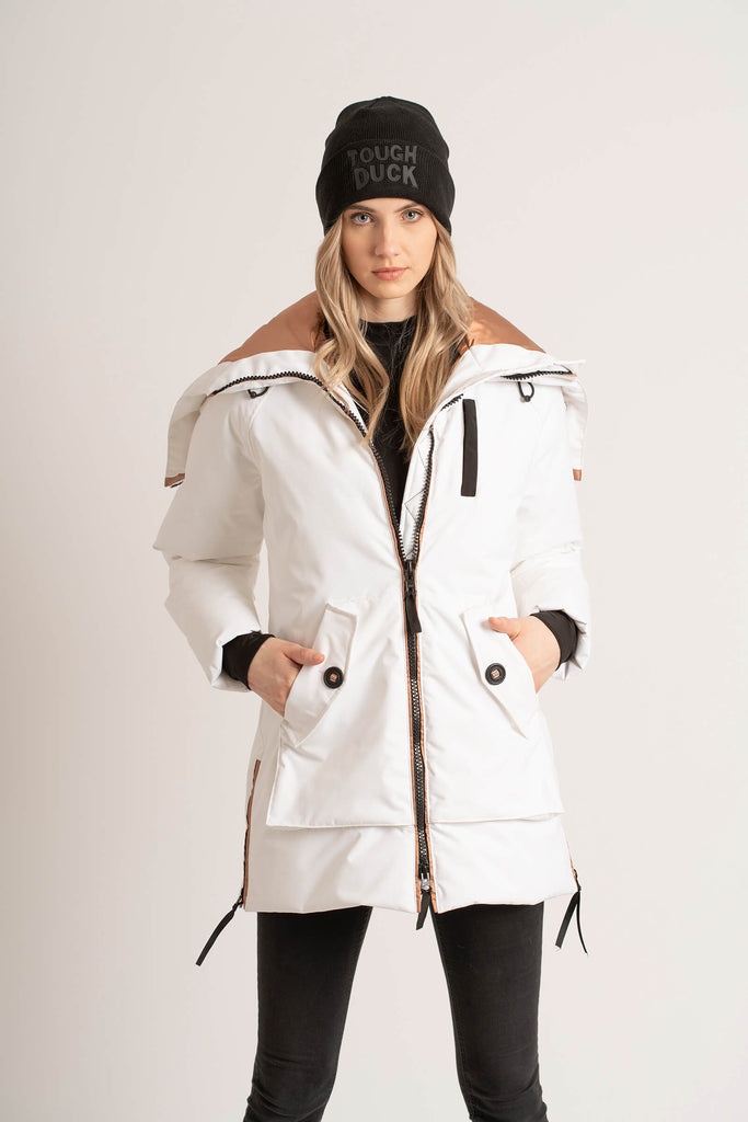 Women wearing a Tough Duck Black Widgeon Mid-Length Parka in white with her hands in her pocket and the jacket half zipped.