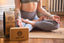 Woman sitting in meditation pose, lotus with yoga world cork mat, wheel and block