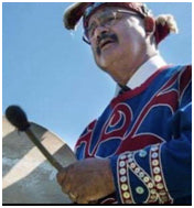 """Picture of Wedlidi Speck in regalia and playing raw hide drum. Author of """"In the Beginning, there Was the First World."""""""