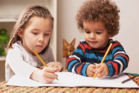 kids drawing with pencil on table