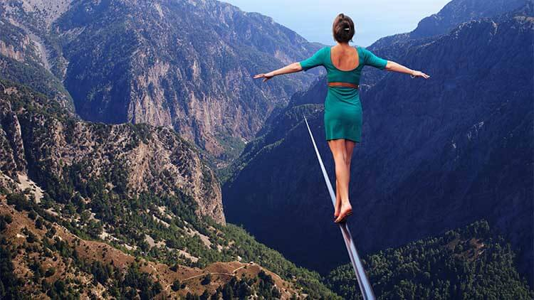 woman balancing on a thin rope between two mountains