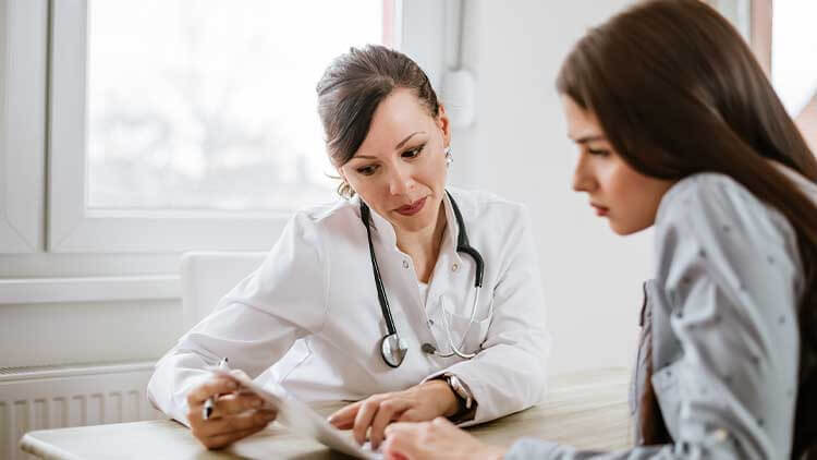 Charming female doctor giving advice to a female patient
