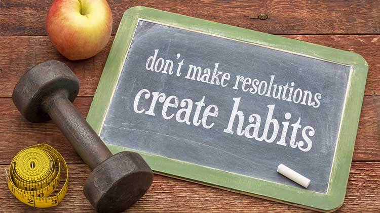 chalkboard sign with writing dont make resolutions, create habits