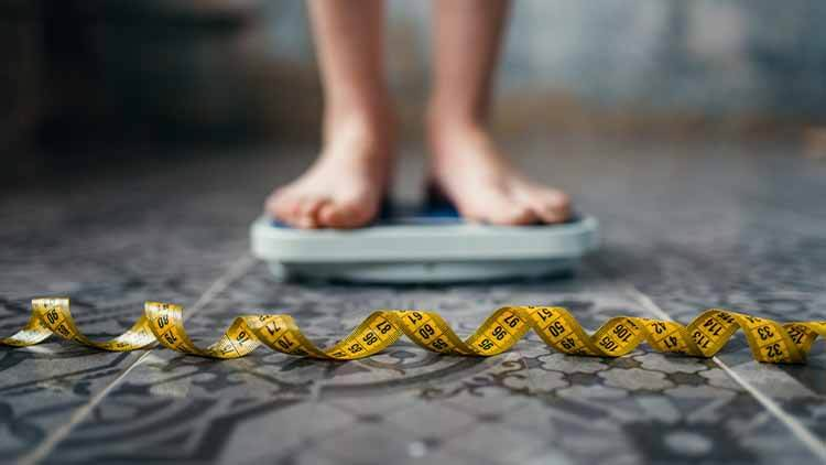 female feet on the scales with a measuring tape laid on the floor in front of her