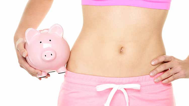 woman wearing a sports bra and pink trusers posing with a piggy bank