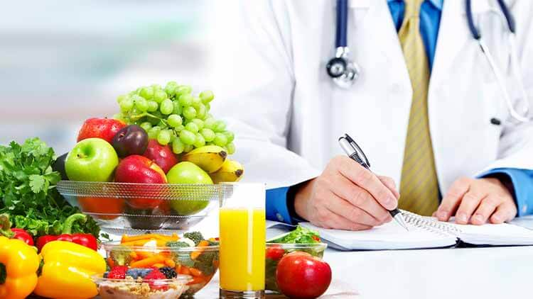 doctor sat writing in his notes next to a bunch of fresh fruit and a freshly squeezed glass of orange juice