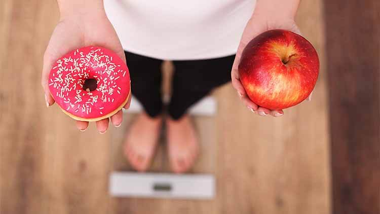 Woman Measuring Body Weight On Weighing Scale Holding Donut and apple