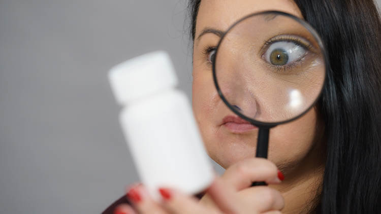 Woman-investigating-ingredients-of-medicines using a magnifying glass