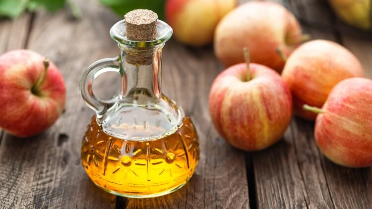 Apple cider vinegar in vial on wooden table next to apples
