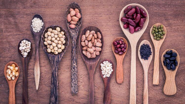 Assorted of beans and lentils in wooden spoons