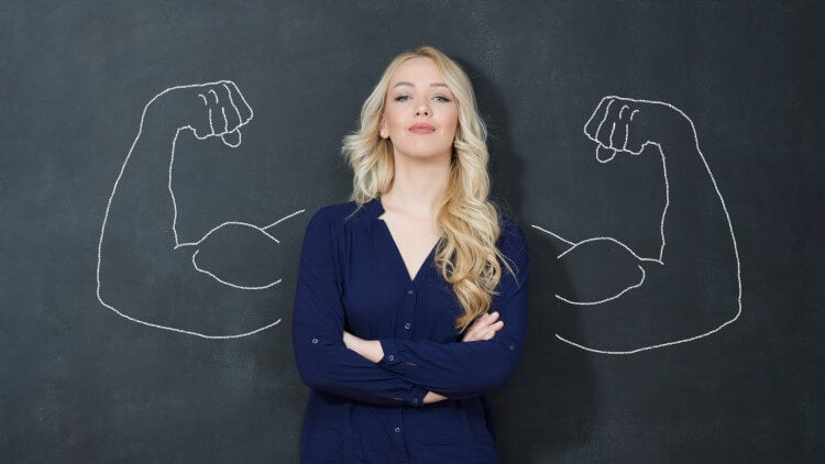 Woman stood in front of chalk board with strong arms drew on