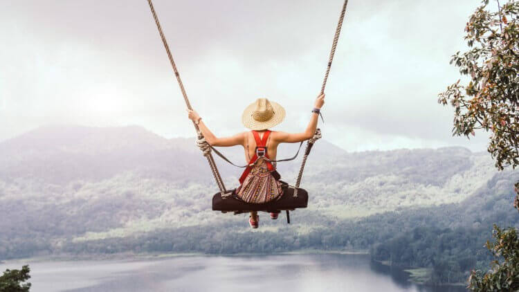 Carefree woman on swing in mountains