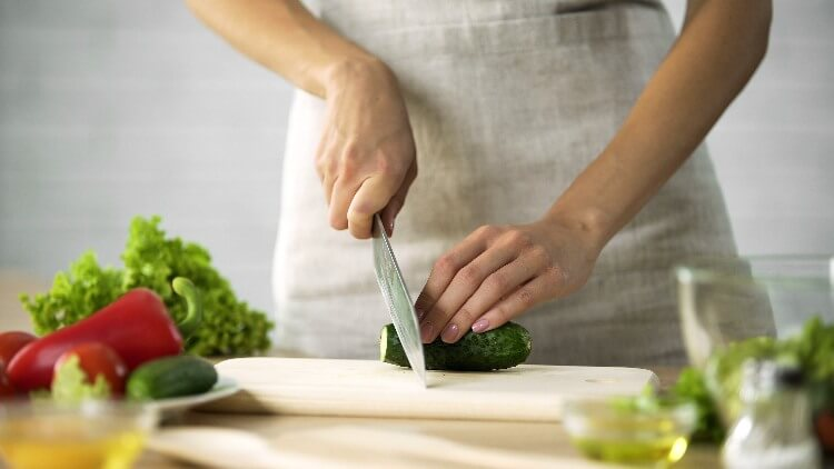 Chef slicing vegetables on cutting board