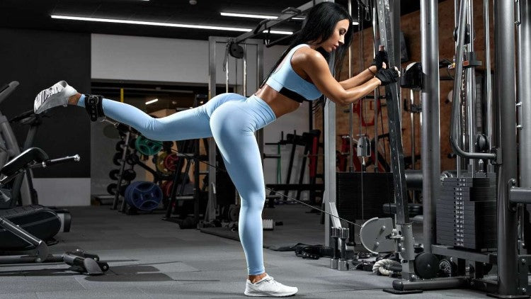 fitness woman exercising glutes via cable lift