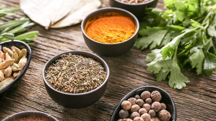 Herbs and spices in bowls on wooden table