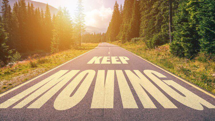 Keep moving written on road going through forest