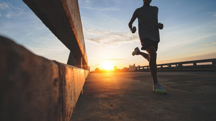 Male athlete running on road in sunlight
