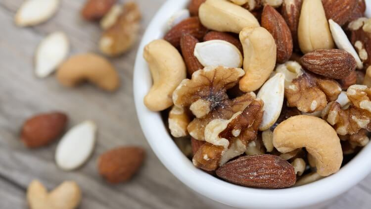 Mixed nuts in white bowl on wooden table