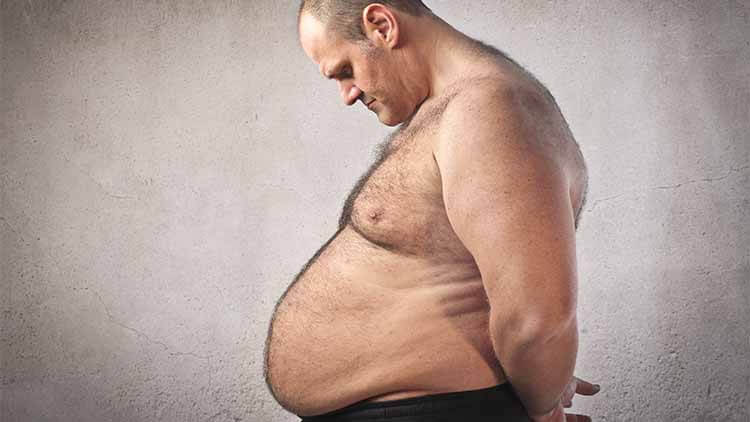 obese man looking down at his stomack feeling not impressed
