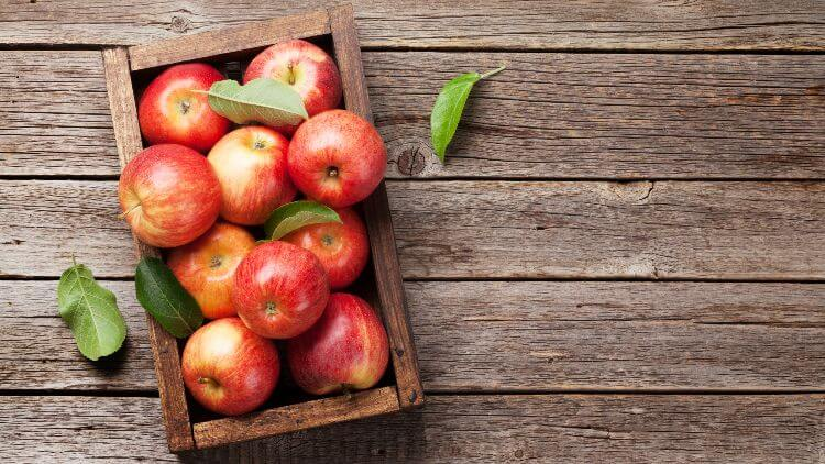 Red apples in wooden box on wooden surface