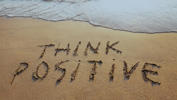 Think positive written into the sand