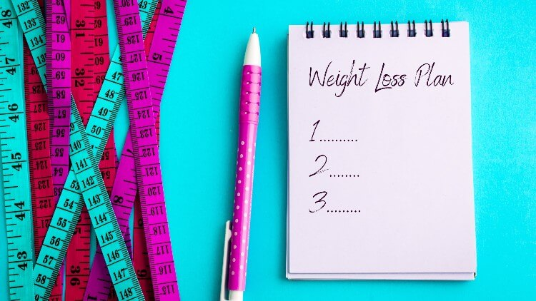 Weight loss plan next to pen and measuring tape