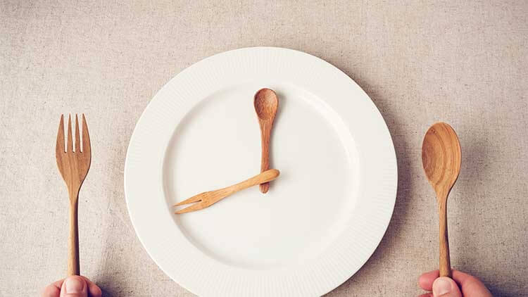 white plate with wooden spoon and a fork