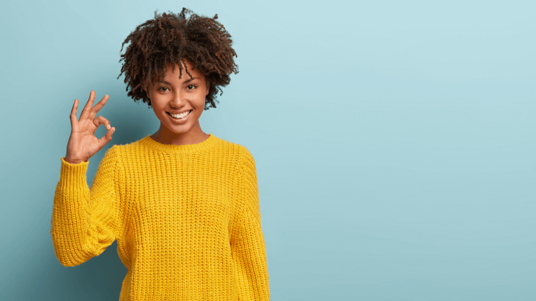 Woman in yellow sweater smiling and giving OK sign