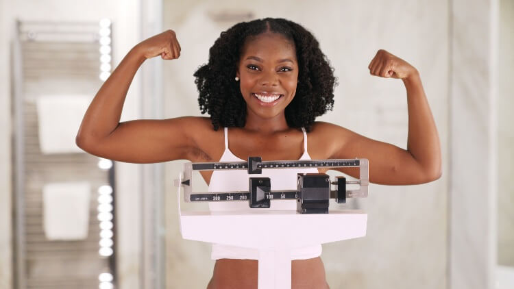 Woman standing on scales cheering showing strong arms