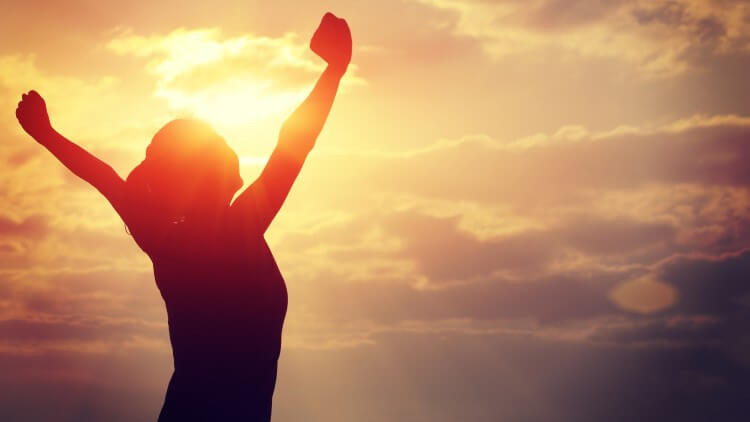 Woman's silhouette cheering in sunset with arms raised