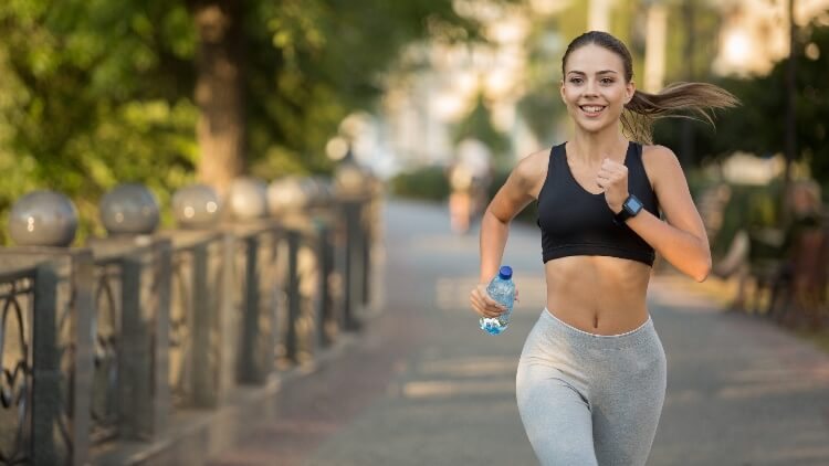 Young fit woman jogging through park