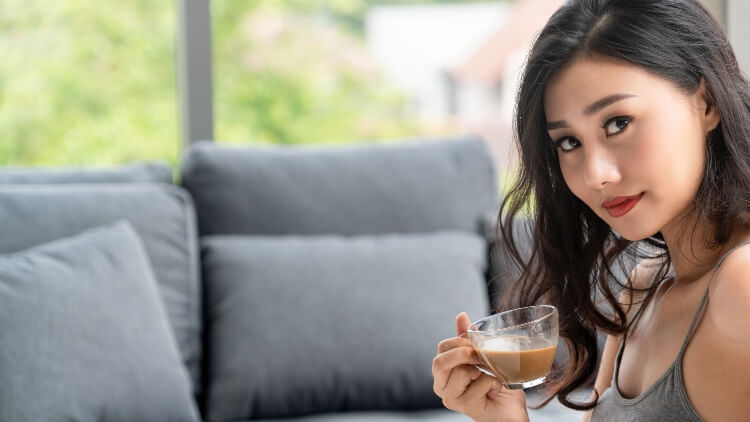 Young woman sat on sofa drinking coffee
