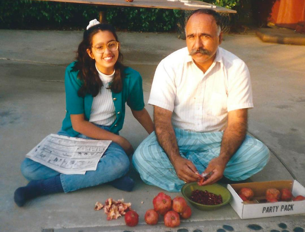 Homa as a teenager seeding pomegranates with her father in their backyard.