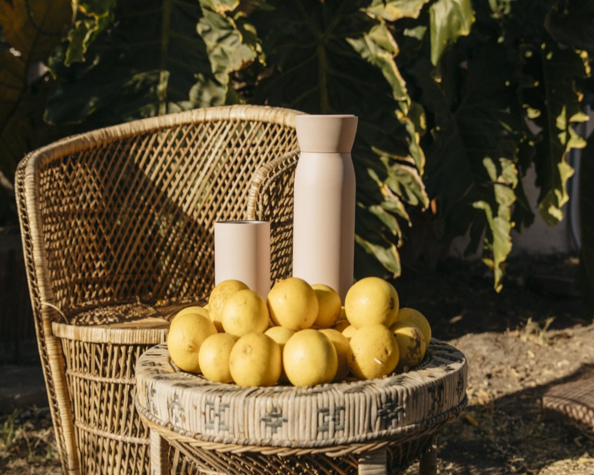 Hitch Bottle and Cup in Pale Blush placed on a wicker table next to a pile of lemons