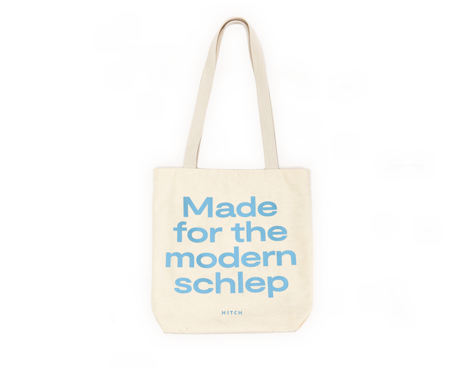 Canvas Tote with shoulder strap, the text says Made for the modern schlep in a pale blue font