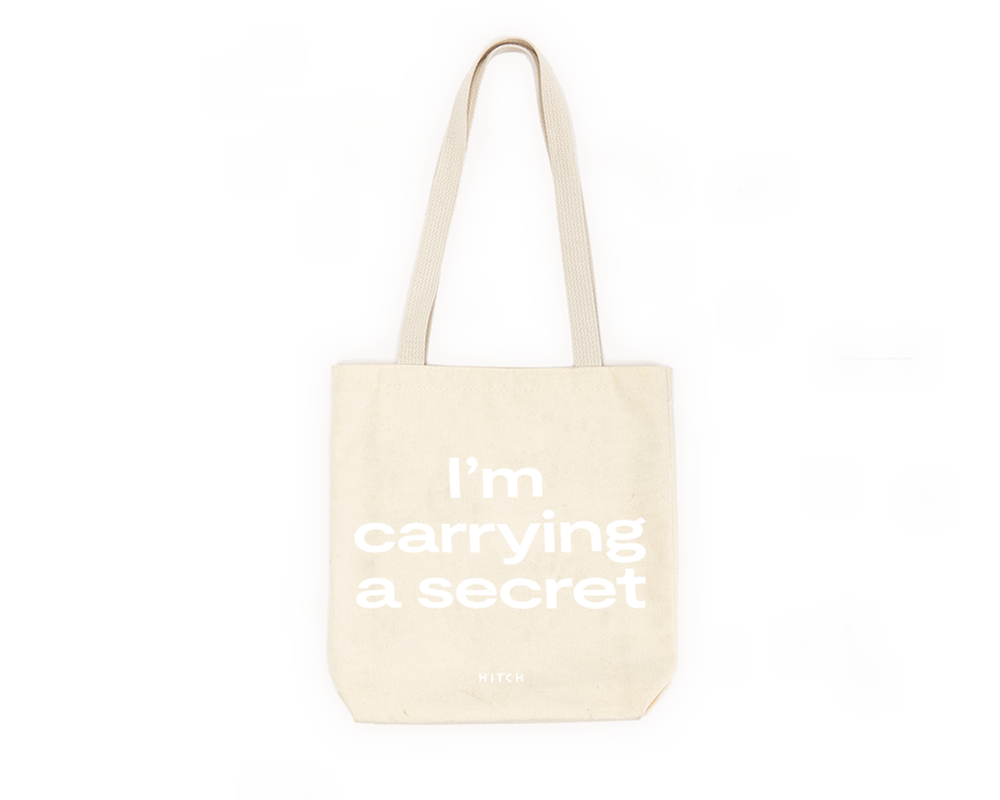"Canvas Tote with shoulder strap, text says ""I'm Carrying a Secret"" in white font"