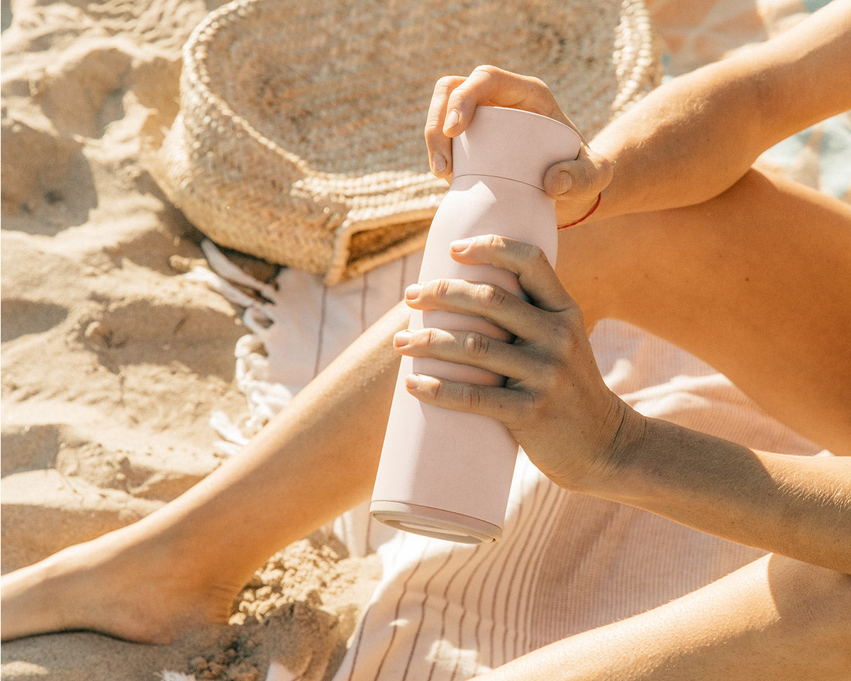 Hitch Bottle and Cup in Pale Blush held by a woman at the beach