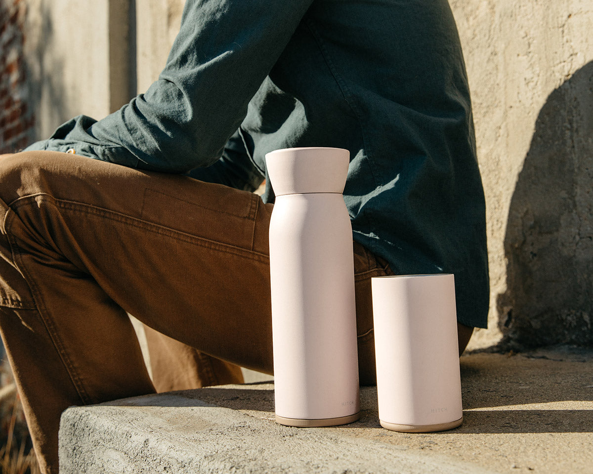 Hitch Bottle and  Hitch Cup in Pale Blush sitting side by side on a concrete stoop next to a seated man