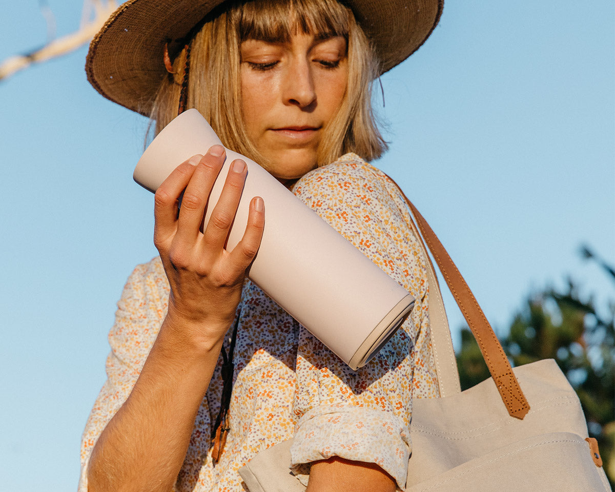 Woman placing Hitch Bottle and Cup in Pale Blush into her bag
