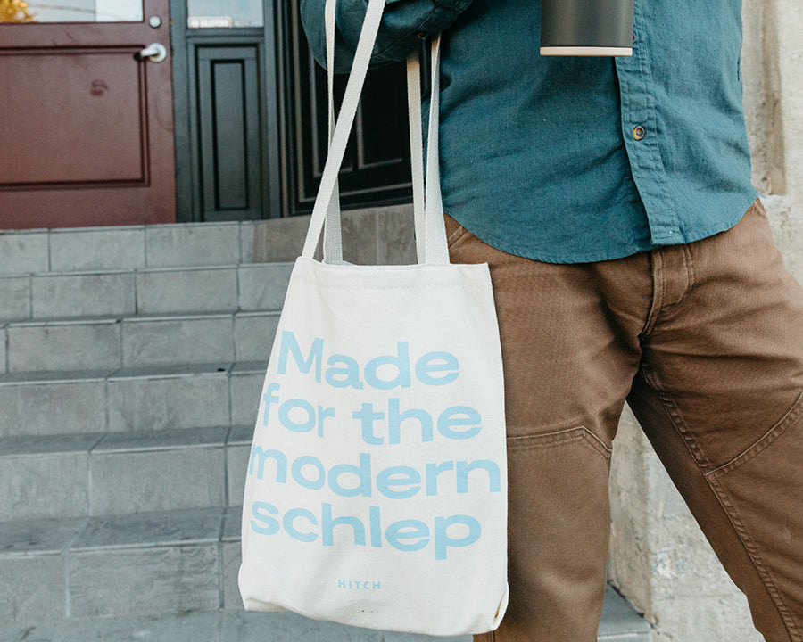 Man Carrying Canvas Hitch Tote with Made for The Modern Schlep printed in light blue, made in america