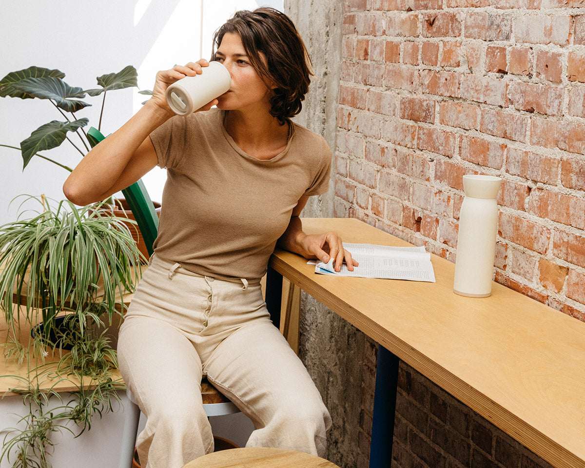 Woman sipping from barista-approved Hitch Cup in a coffee shop with exposed brick and indoor plants