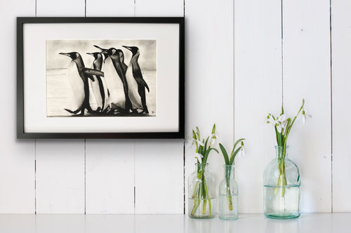 framed hand drawn image print of 2 penguins hung above shelf next to flower vases