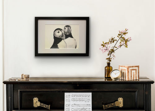 framed hand drawn image of 2 puffins hung on wall above piano