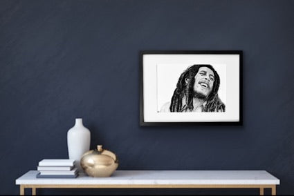 Beautiful , detailed hand drawn drawing in black and white of Bob Marley . Drawn in charcoal and graphite . It is a beautiful print. Beautifully framed in a black hamdmade frame and mounted in a hand cut white mount