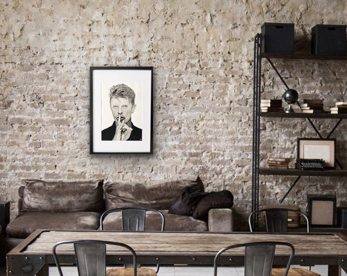 hand drawn framed image of david bowie above sofa