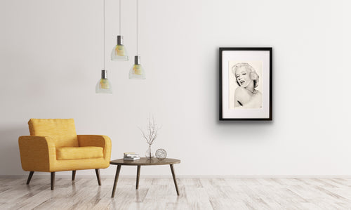 hand drawn framed image of marilyn monroe on wall above table and chairs