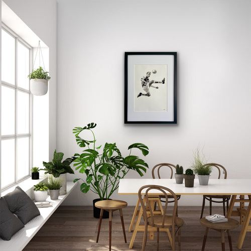 hand drawn framed image of footballer denis bergkamp on wall above table and chairs