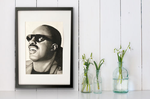 hand drawn framed image of stevie wonder hung on wall nect to flower vases